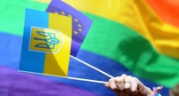 A protester holds the flags of Ukraine, bearing the country's coat of arms, and the  European Union in front of a rainbow flag, as members and supporters of the LGBT (Lesbian-Gay-Bisexual-Transgender) community take part in a May Day rally in Saint Petersburg on May 1, 2015. AFP PHOTO / OLGA MALTSEVA        (Photo credit should read OLGA MALTSEVA/AFP/Getty Images)