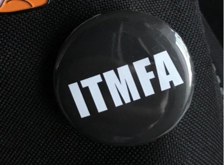 round black button bearing the letters ITMFA in white, pinned to black cloth