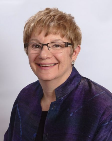 woman smiling. she has short hair, glasses and is wearing a purple jacket