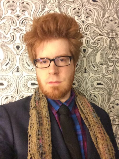 man with red hair, glasses and a beard wearing a dark suit and scarf