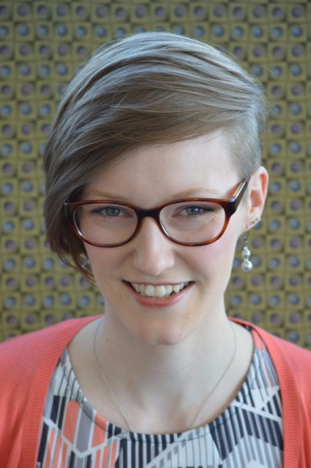 woman with light brown hair, glasses, wearing a patterned shirt and pink sweater.