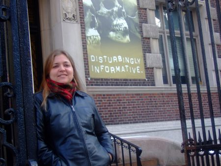 woman with shoulder-length brown hair, wearing a black leather jacket and red scarf, in front of a sign that says disturbingly informative